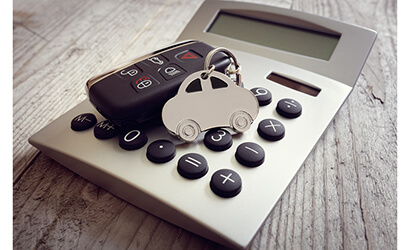 Car shaped key-ring on top of calculator