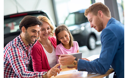 Happy family in car dealership, signing a car lease contract