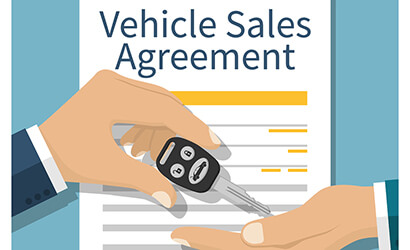 Hand holding a car key for Lease in front of a loan contract agreement