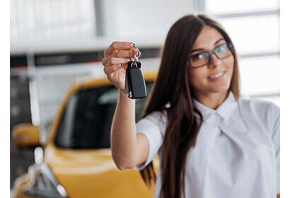 Leasing a car made simple with a female holding car keys in front of a yellow car