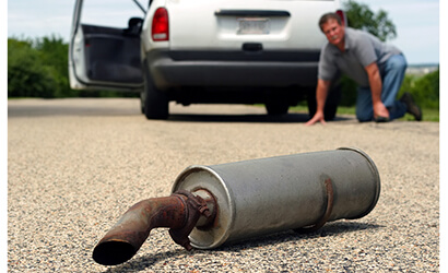 a man on the ground trying to find the cars muffler