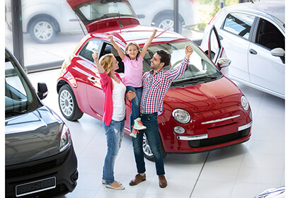 excited family standing next to a new car