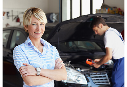 a woman standing in front of a car shop as a man inspects it